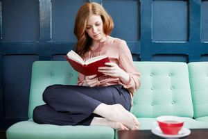 Woman-reading-a-book-on-sofa